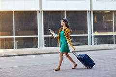 Happy young woman with travel bag and map in city. Travel, trip, tourism, people and vacation concept - happy young woman with carry-on travel bag and map Royalty Free Stock Images