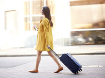 Happy young woman with travel bag and map in city. Travel, trip, tourism, people and vacation concept - happy young woman with carry-on travel bag and map Stock Photo
