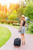 happy young woman with travel bag walking in the park Stock Photos
