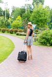 happy young woman with travel bag walking in the park Royalty Free Stock Photo