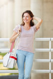 Happy young woman traveler smiling with bag outdoors Royalty Free Stock Photography