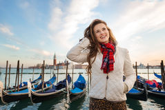 Happy young woman traveler standing on embankment in Venice Stock Photo
