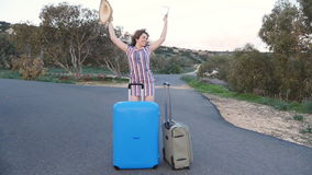 Happy young woman traveler with suitcase dancing stock video