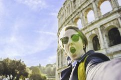 Happy young woman travelling Europe taking selfie in front of famous landmark the Coliseum, Rome, Italy stock photos