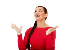 Happy young woman trying to catch something falling from the sky Royalty Free Stock Photos