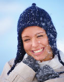 Happy young woman trying to keep warm in the snow Stock Photo