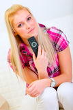 Happy young woman with TV remote control Stock Photography