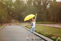 Happy young woman with umbrella under rain. In park royalty free stock photo