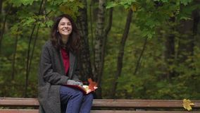 Happy young woman under falling leaves in a park. Happy young woman in a thick coat is smiling and looking at camera under falling leaves in an autumn park stock video
