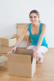 Happy young woman unwrapping boxes in new house Royalty Free Stock Photos