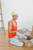 Happy young woman unwrapping boxes in new house Royalty Free Stock Photography