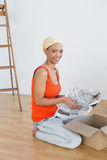 Happy young woman unwrapping boxes in new house Stock Images