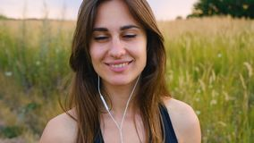 Happy young woman use smartphone and headphone standing in field at sunset, healthy lifestyle. Sportywoman runner using. Happy woman use smartphone and headphone stock video