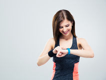 Happy young woman using activity tracker. Over gray background Royalty Free Stock Photo
