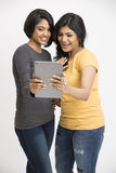 Happy young woman using digital tablet Royalty Free Stock Images