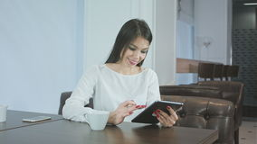 Happy young woman using digital tablet in a coffee shop stock footage