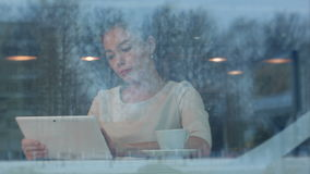 Happy young woman using digital tablet in a coffee shop. Viewed through the window. Professional shot on BMCC RAW with high dynamic range. You can use it e.g stock video footage
