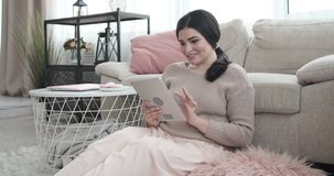 Businesswoman using digital tablet at home. Happy young woman using digital tablet at home stock video