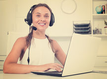 Happy young woman using headset at call center Stock Image
