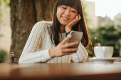 Happy young woman using her cellphone at cafe Royalty Free Stock Photography