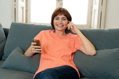 Happy young woman using her smart phone sitting on sofa at home. In leisure and spare time concept stock images