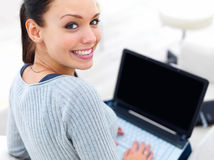 Happy young woman using laptop Stock Image