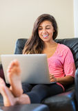 Happy young woman using a laptop computer Stock Image