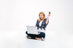 Happy young woman using laptop computer while holding debit card. Photo of happy young woman using laptop computer  on a white background while holding debit Royalty Free Stock Photography