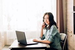 Happy young woman using laptop at home. Attractive woman having happy look while speaking over smartphone, using black laptop. People, technology, lifestyle stock image