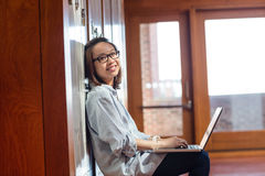Happy young woman using laptop in locker room Stock Photos