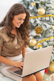 Happy young woman using laptop near christmas tree Stock Images