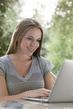 Happy young woman using laptop outdoors Stock Photo