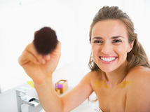 Happy young woman using makeup brush Stock Images