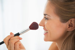 Happy young woman using makeup brush Royalty Free Stock Images