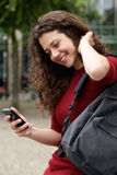 Happy young woman using mobile phone outdoors. Close up portrait of happy young woman using mobile phone outdoors Royalty Free Stock Image
