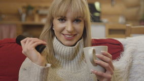 Happy young woman using remote control to change channel while sitting at home. Beautiful blonde woman holding cup of tea or coffee and relaxing on a red sofa stock video footage