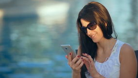 Happy young woman using a smart phone near the swimming pool stock video