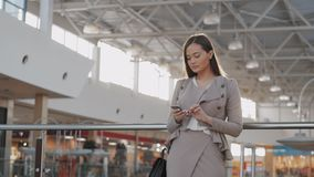 Happy young woman using smart phone in shopping mall. Businesswoman freelancer with smartphone in airport terminal. stock video