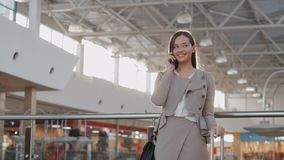 Happy young woman using smart phone in shopping mall. Businesswoman freelancer with smartphone in airport terminal. stock video footage