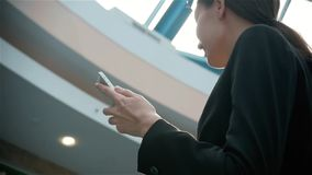 Happy young woman using smart phone in shopping mall. Businesswoman freelancer with smartphone in airport terminal