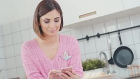 Woman using smartphone in kitchen sending message on social media. Happy, young woman using smartphone and drinking coffee in kitchen. Attractive woman at home stock video