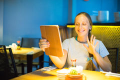 Happy young woman using tablet computer in a cafe Stock Image