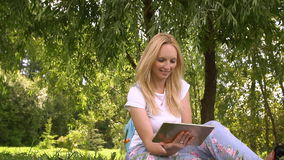Happy young woman using tablet computer in the park, slow motion. Happy young woman using tablet computer in the park, slow motion stock video footage