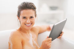 Happy young woman using tablet pc in bathtub Royalty Free Stock Images