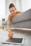 Happy young woman using tablet pc while laying on sofa Royalty Free Stock Photo