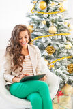 Happy young woman using tablet pc near christmas tree Royalty Free Stock Photography