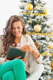Happy young woman using tablet pc near christmas tree Royalty Free Stock Image