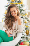 Happy young woman using tv remote control near christmas tree Stock Image