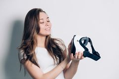 Happy young woman using a virtual reality headset. smiling, looking at reality glasses. stock image