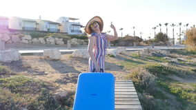 Happy young woman on vacation with a suitcase. Travel concept stock video